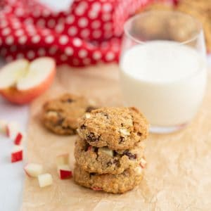 A stack of three oat meal cookies sitting on crinkled parchment paper with a glass of milk in the background.