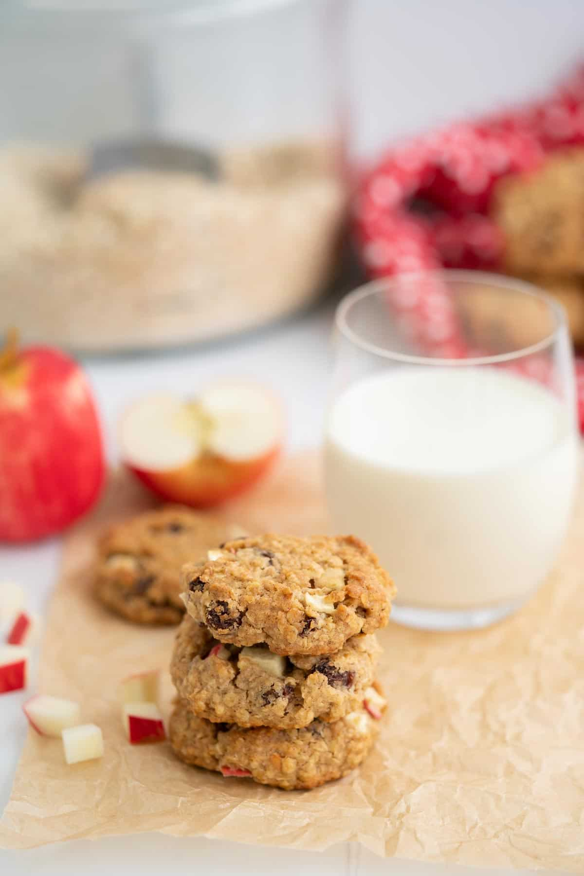 A stack of three oat meal cookies sitting on crinkled parchment paper with a glass of milk, apples and a jar of rolled oats in the background.