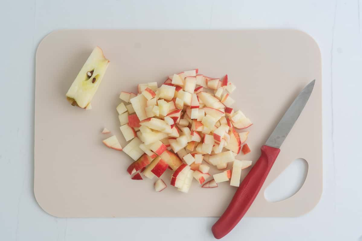 A chopping board covered in diced apple with a small red handled fruit knife.