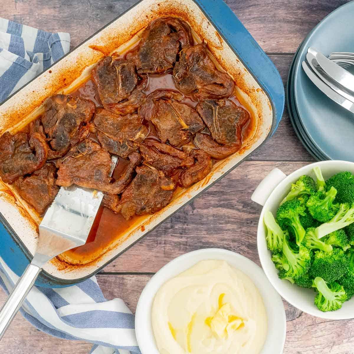 A cermic backing dish of marinaded lamb chops, alongside a bowl of mashed potato and broccoli.