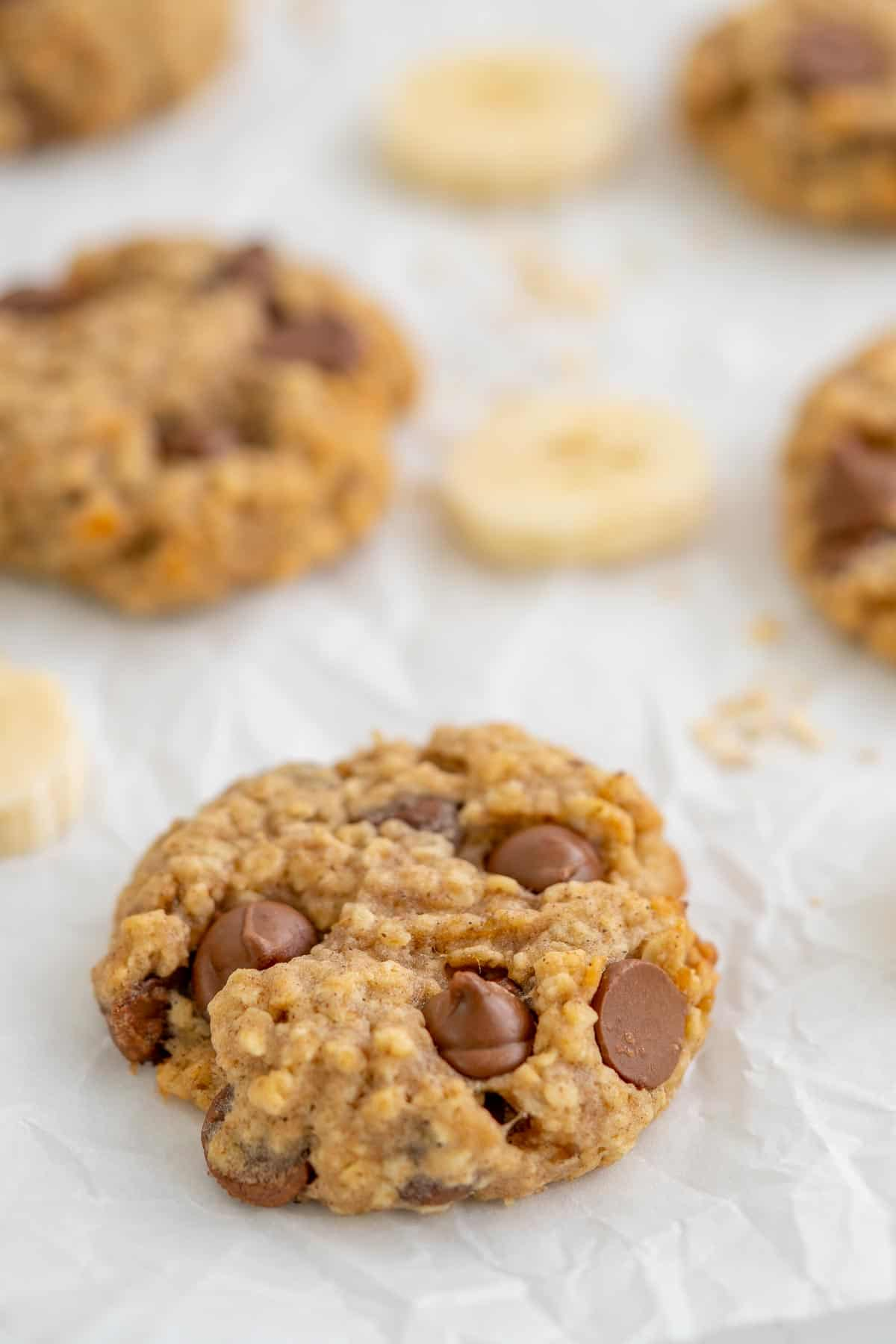 A banana oatmeal cookie on crinkled baking paper, with slices of banana and a scattering of rolled oats and chocolate drops.