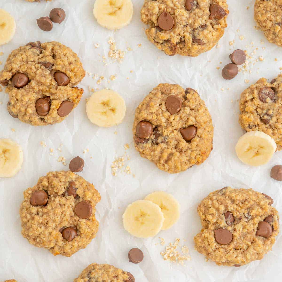 Banana oatmeal cookies laid out on baking paper, with slices of banana and a scattering of rolled oats and chocolate drops.