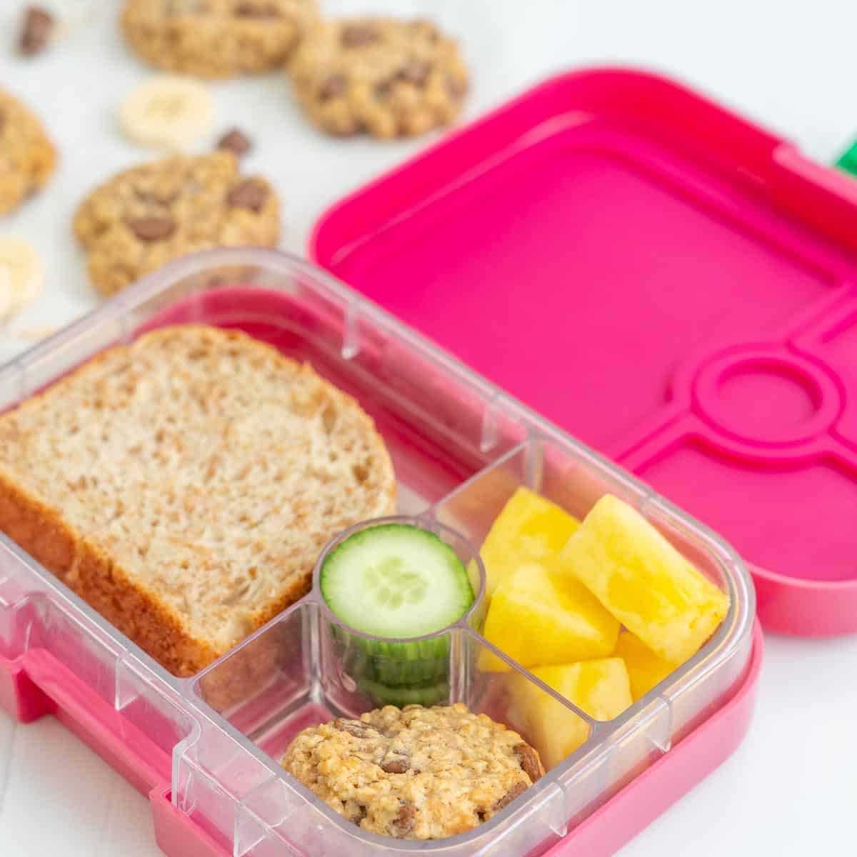 A pink bento style lunchbox, packed with a sandwich, pineapple, oatmeal cookie and cucumber slices.