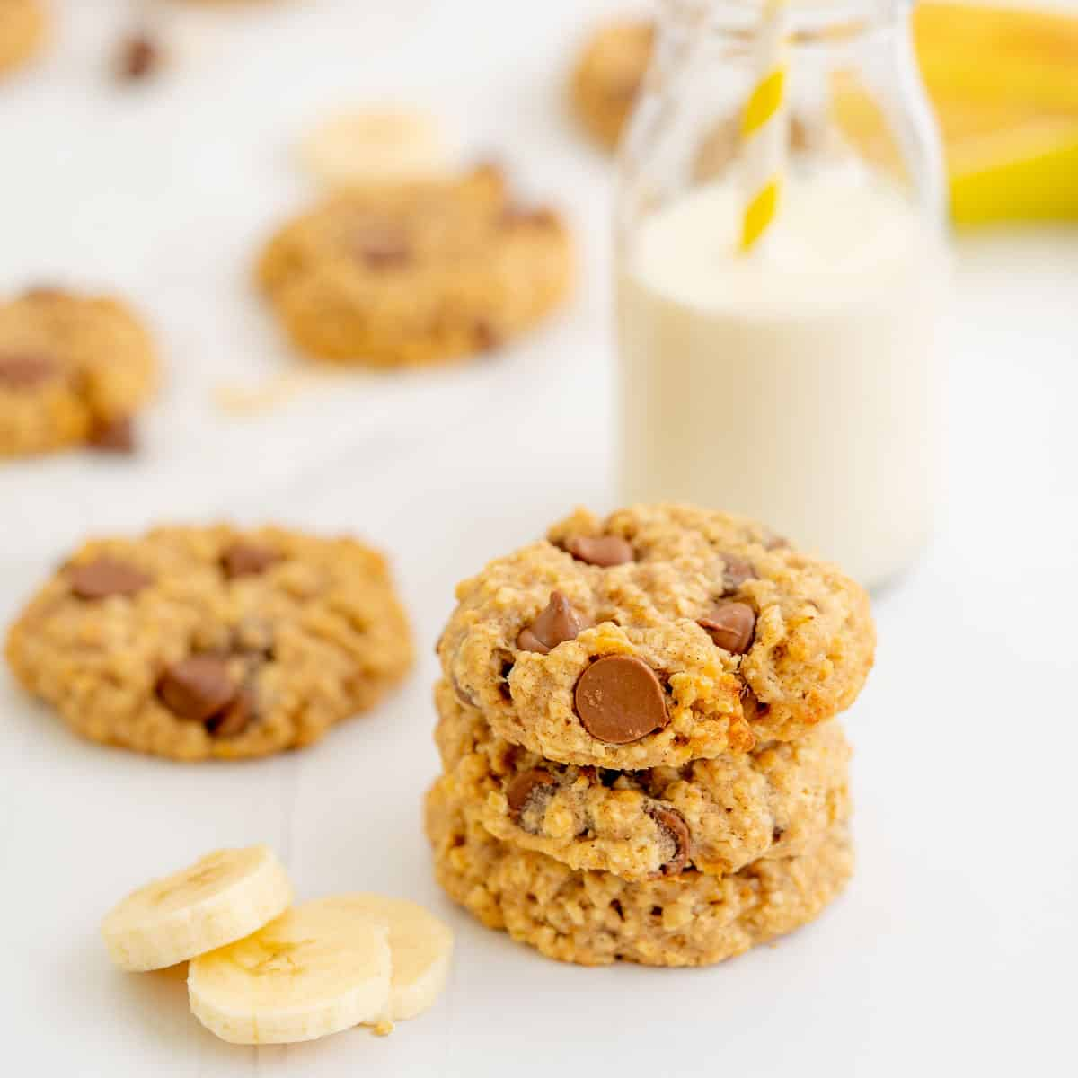 Three thick oat cookies stacked in a tower next to slices of banana.