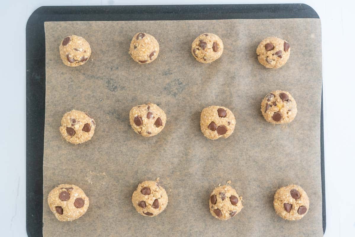 12 balls of choc chip oatmeal cookie dough on a lined baking tray.