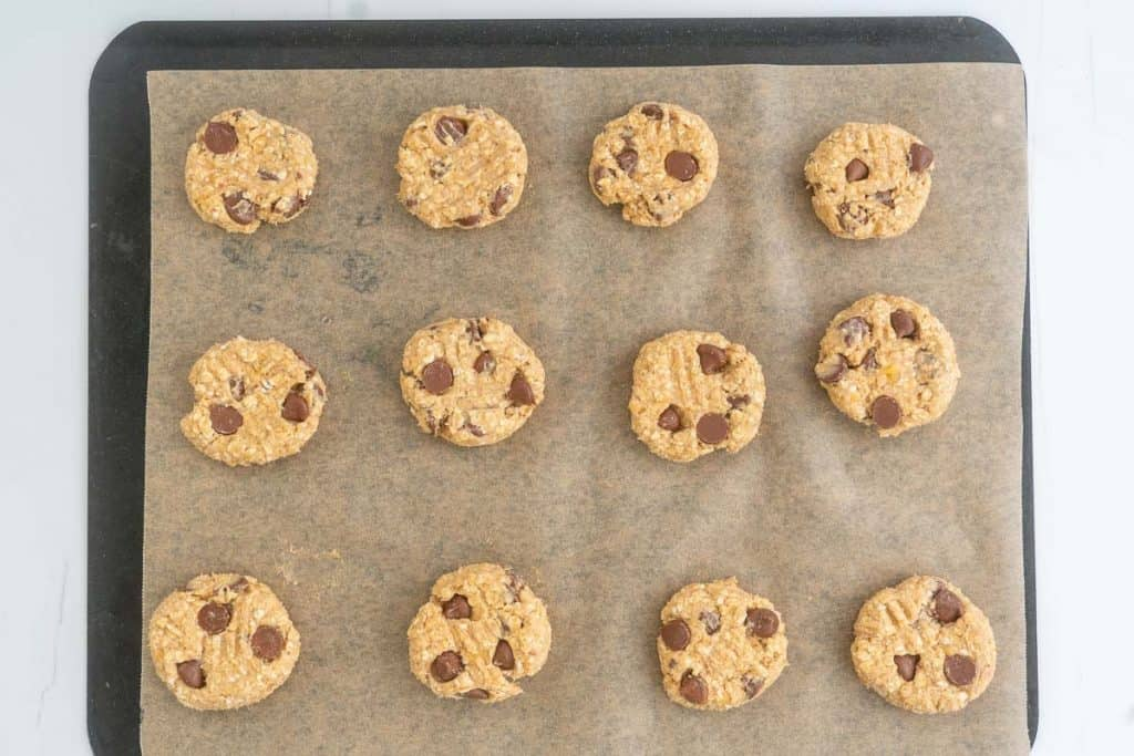 Banana oatmeal cookies ready on a lined baking tray ready to be baked,