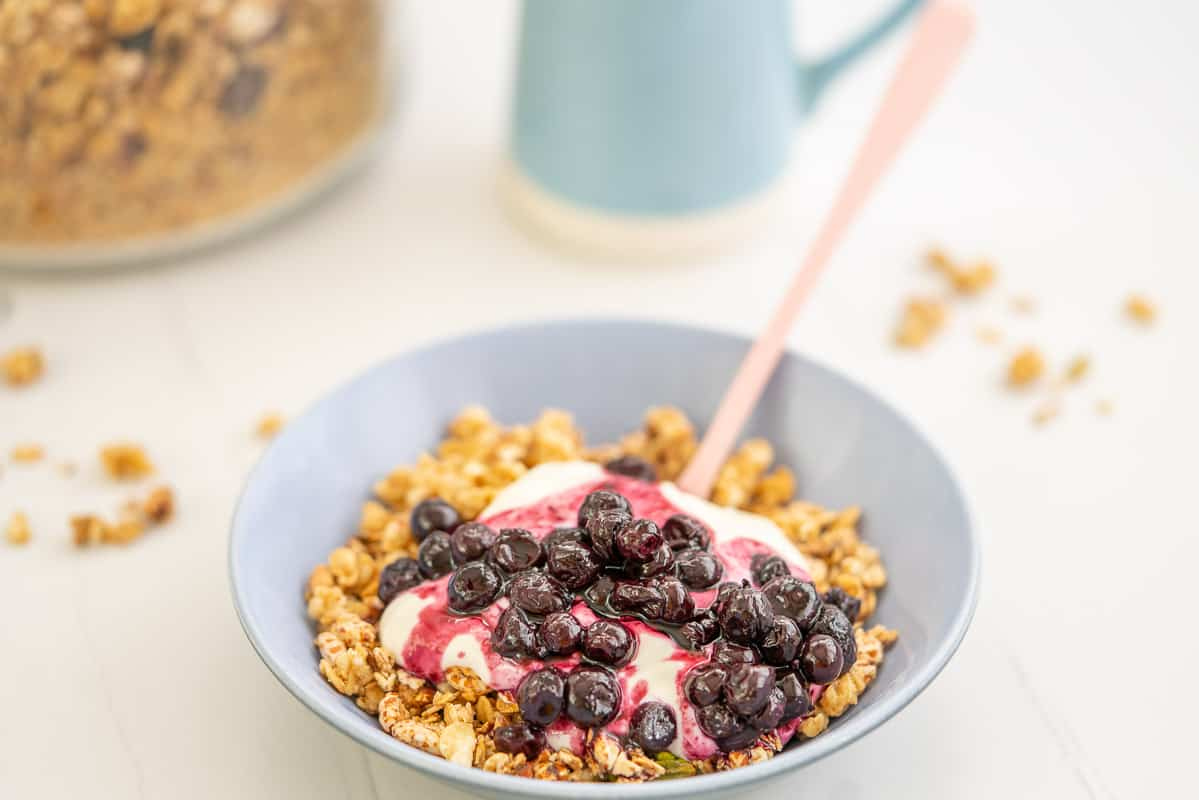 A bowl of granola topped with yoghurt and blueberrysauce.