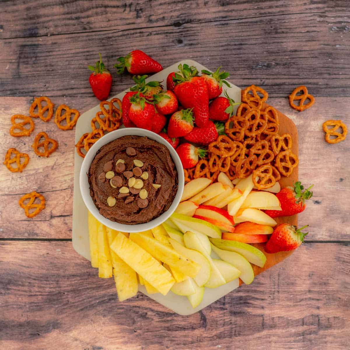 A platter of fresh fruit and pretzels with a bowl of chocolate hummus.