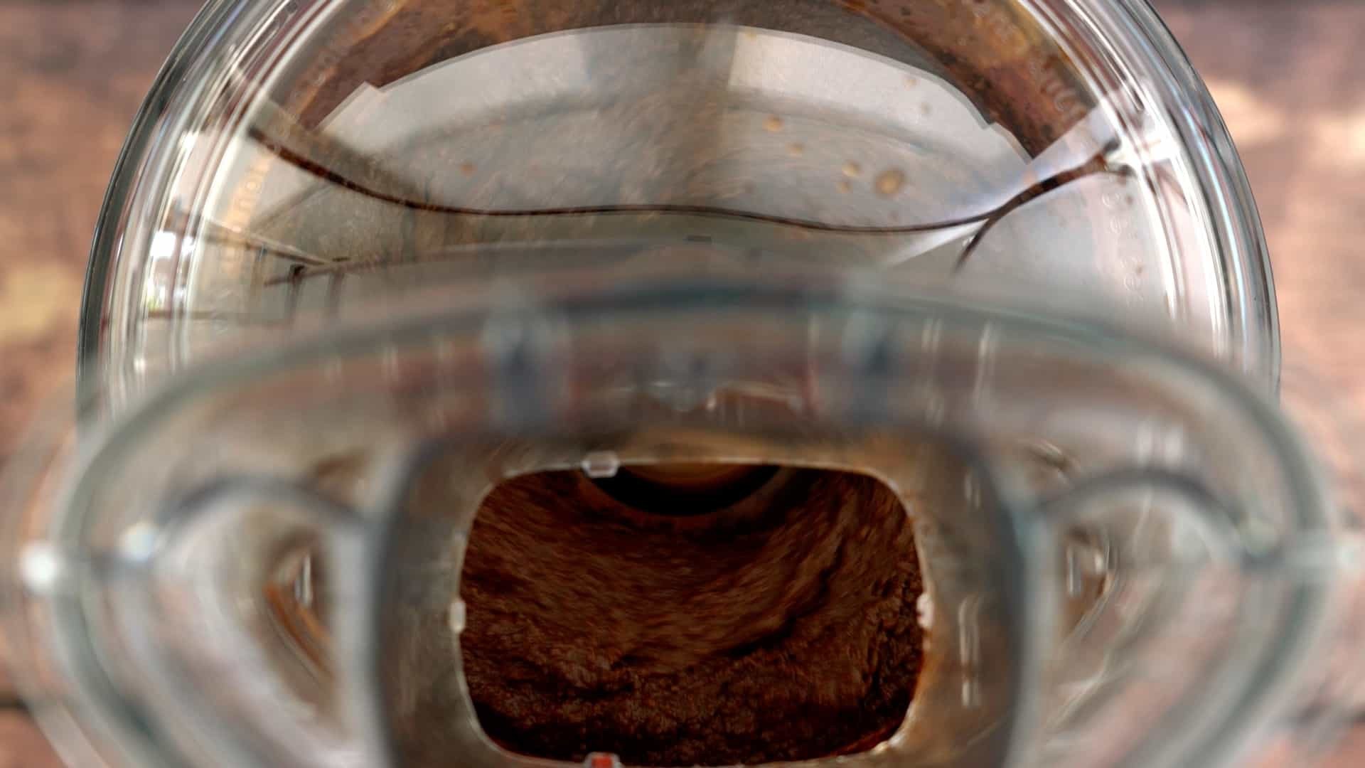 A food processor blending a smooth chocolate dip.