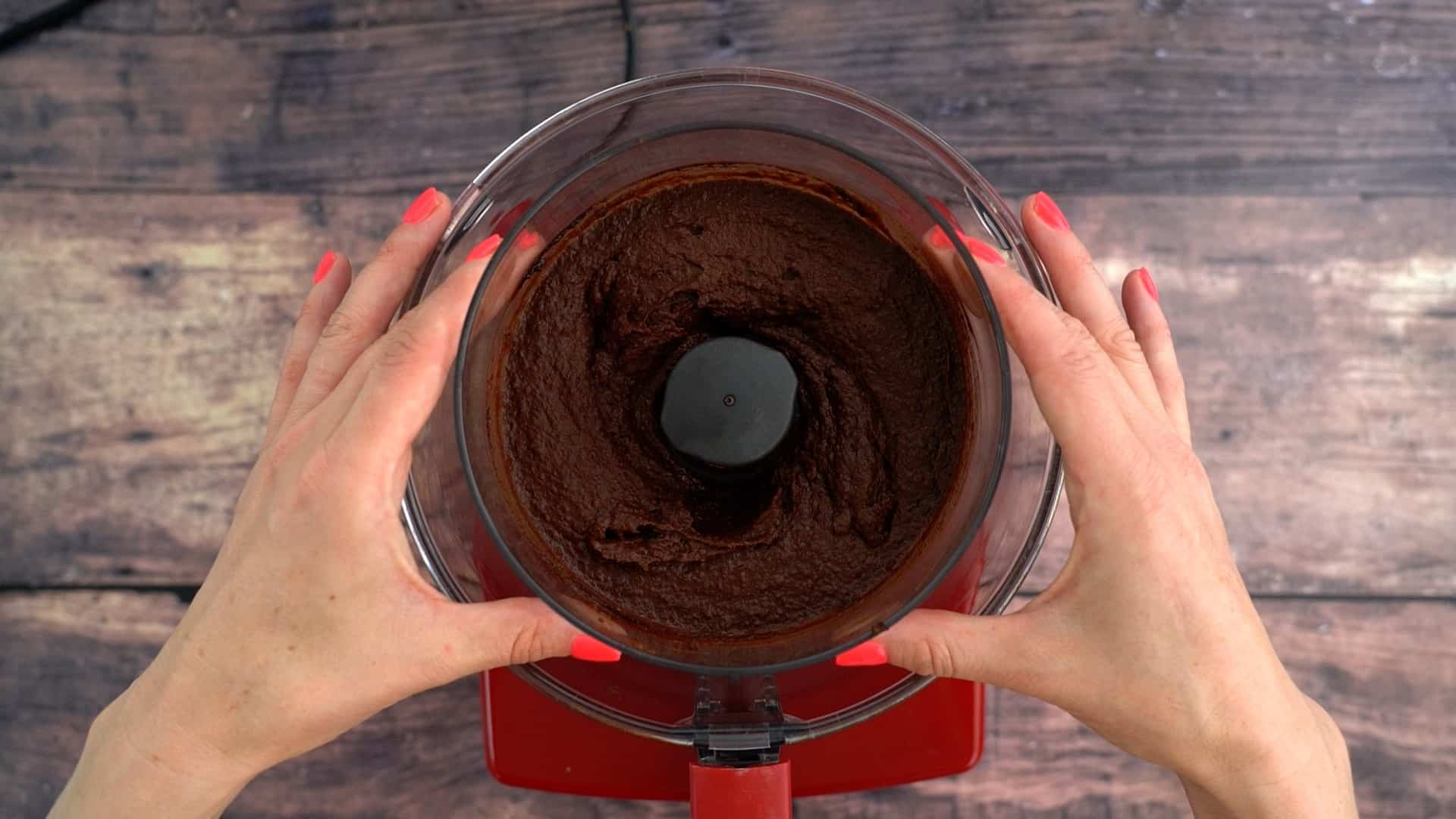 Smooth chocolate chickpea dip in the small bowl of a food processor.