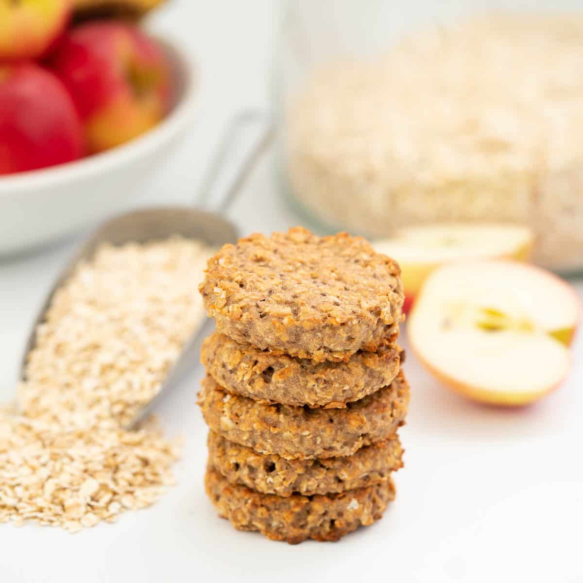 A stack of 5 oatmeal toddler cookies on a bench top with rolled oats and apples in the background.