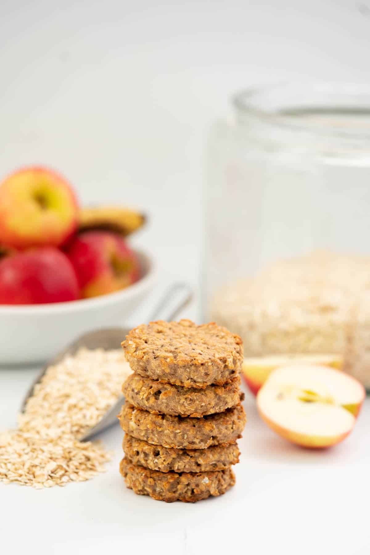 A stack of 5 oatmeal toddler cookies on a bench top with rolled oats and apples in the background