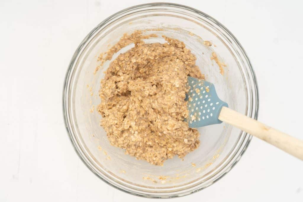 Applesauce oatmeal cookie dough in a glass mixing bowl.