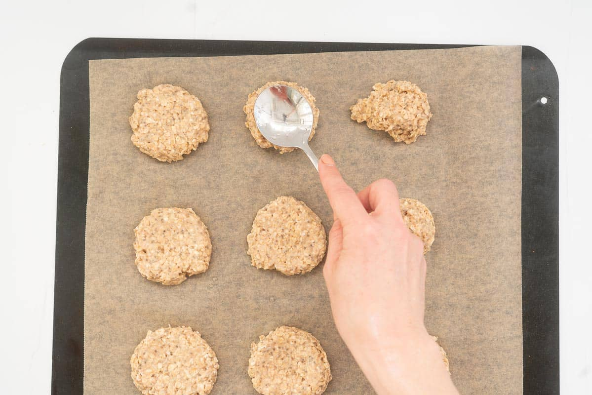Balls of cookie dough on a baking paper lined tray being flattened with the back of a spoon.