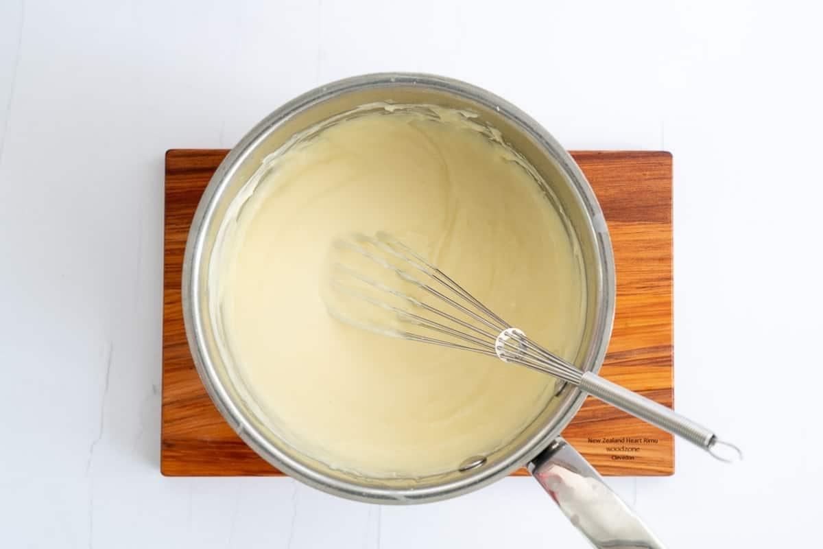 A saucepan of smooth cheese sauce.