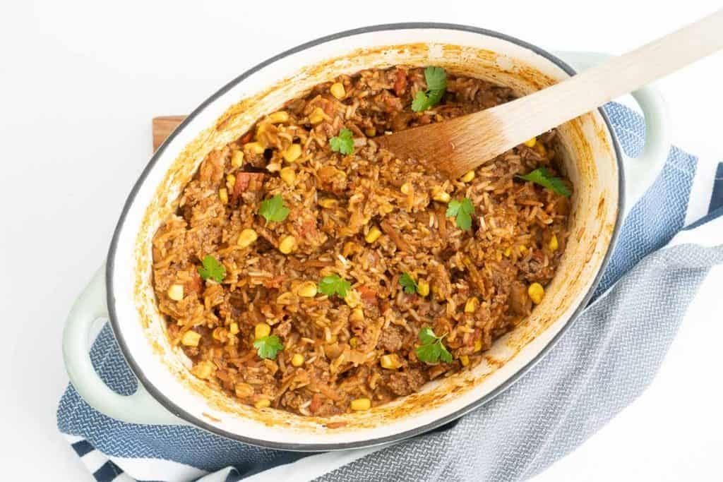 A dutch oven filled with Mexican mince and rice garnished with coriander leaves.