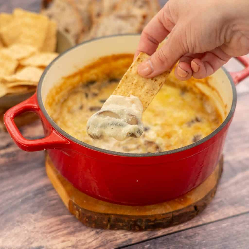 A hand scooping baked cheese dip fro a red dish with a corn tortilla chip.