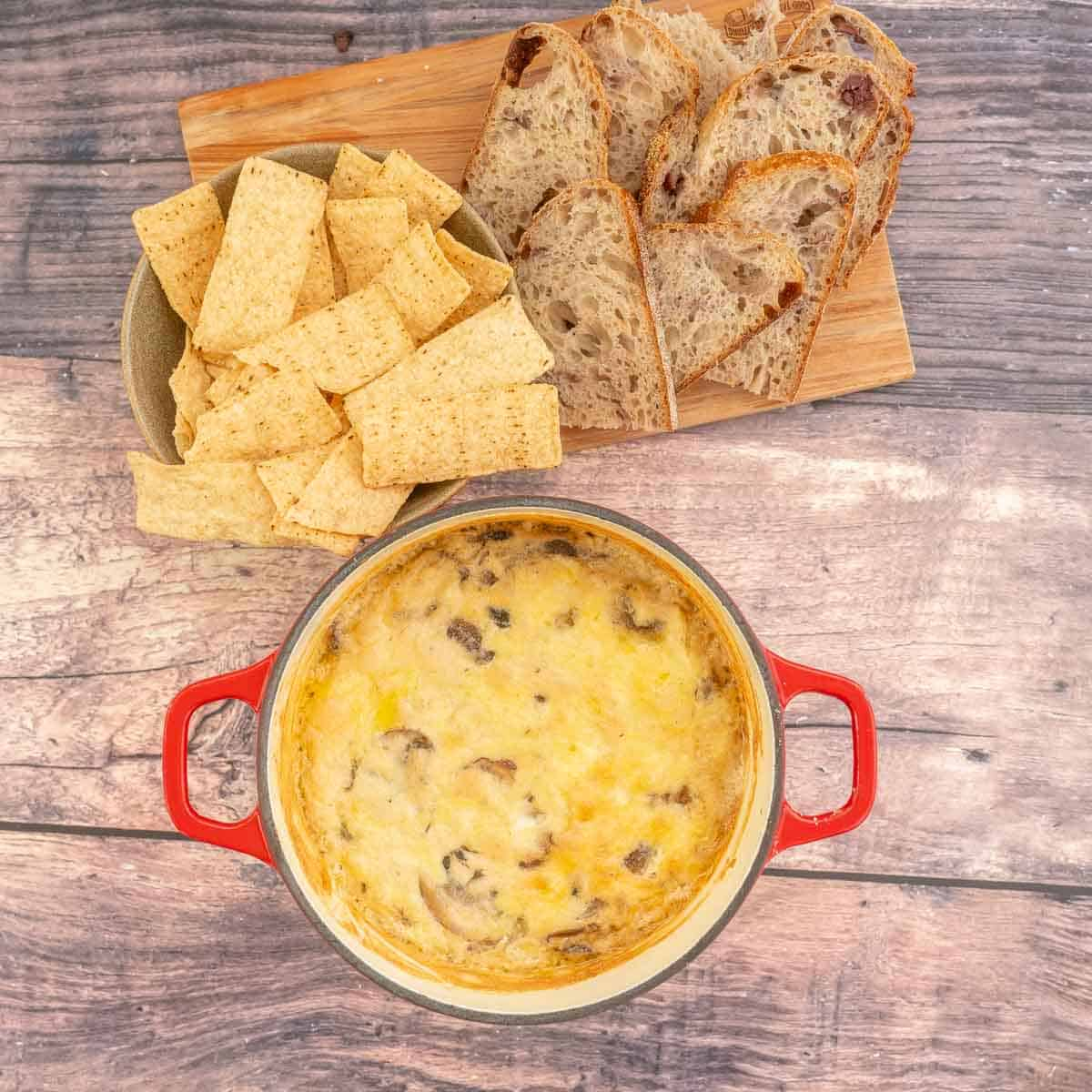 A baked cheese dip with a wooden board of chips and crusty bread.