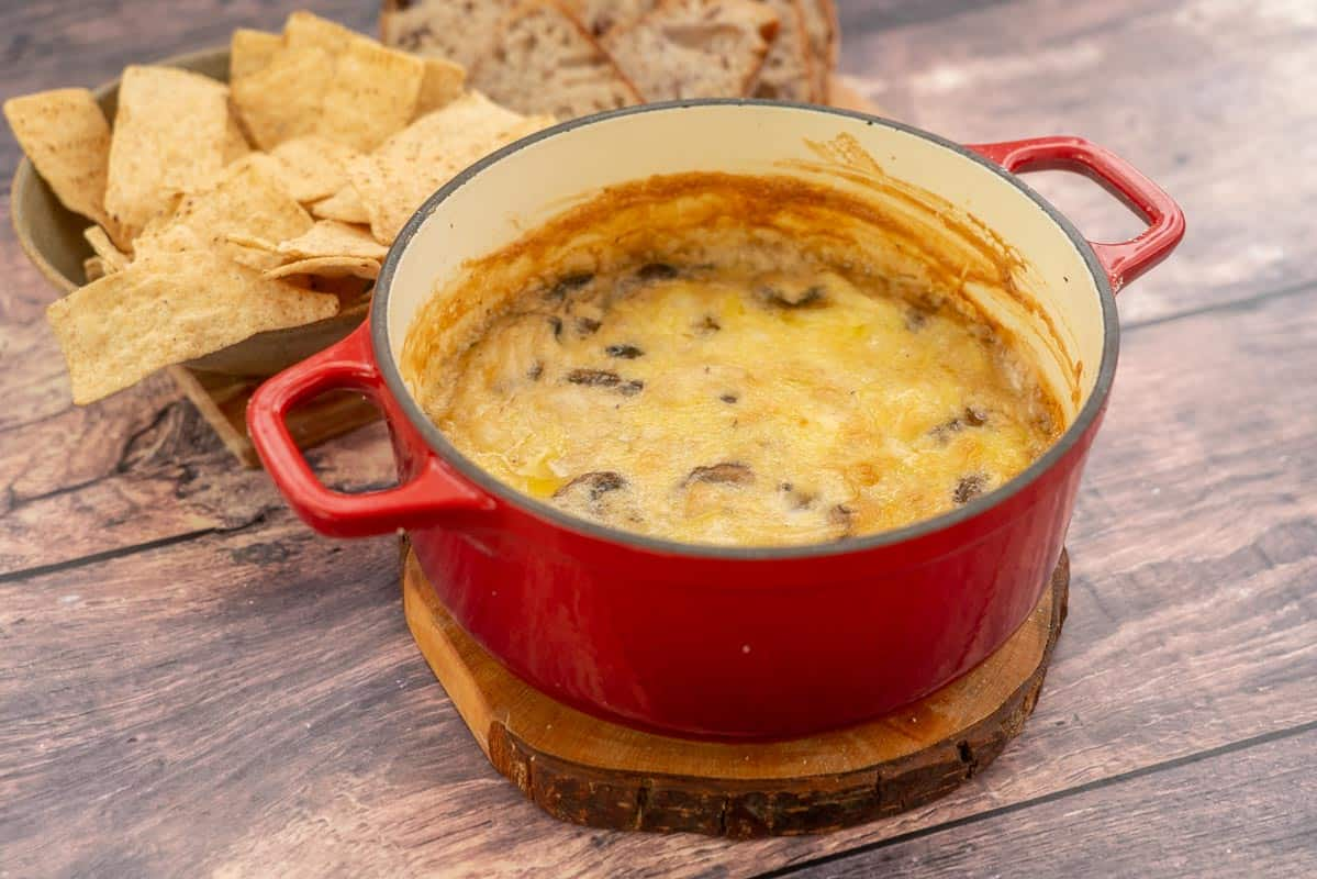 A warm cheese dip in a red ceramic baking dish ready to be served.