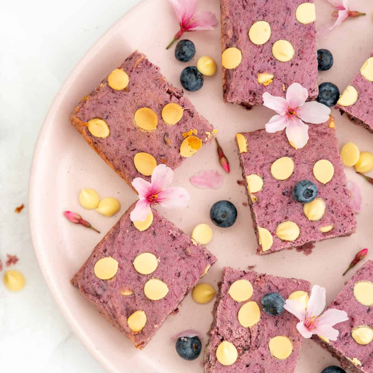 Purple cookie bars on a pink plate scattered with blueberries, pink flours and white chocolate chips.
