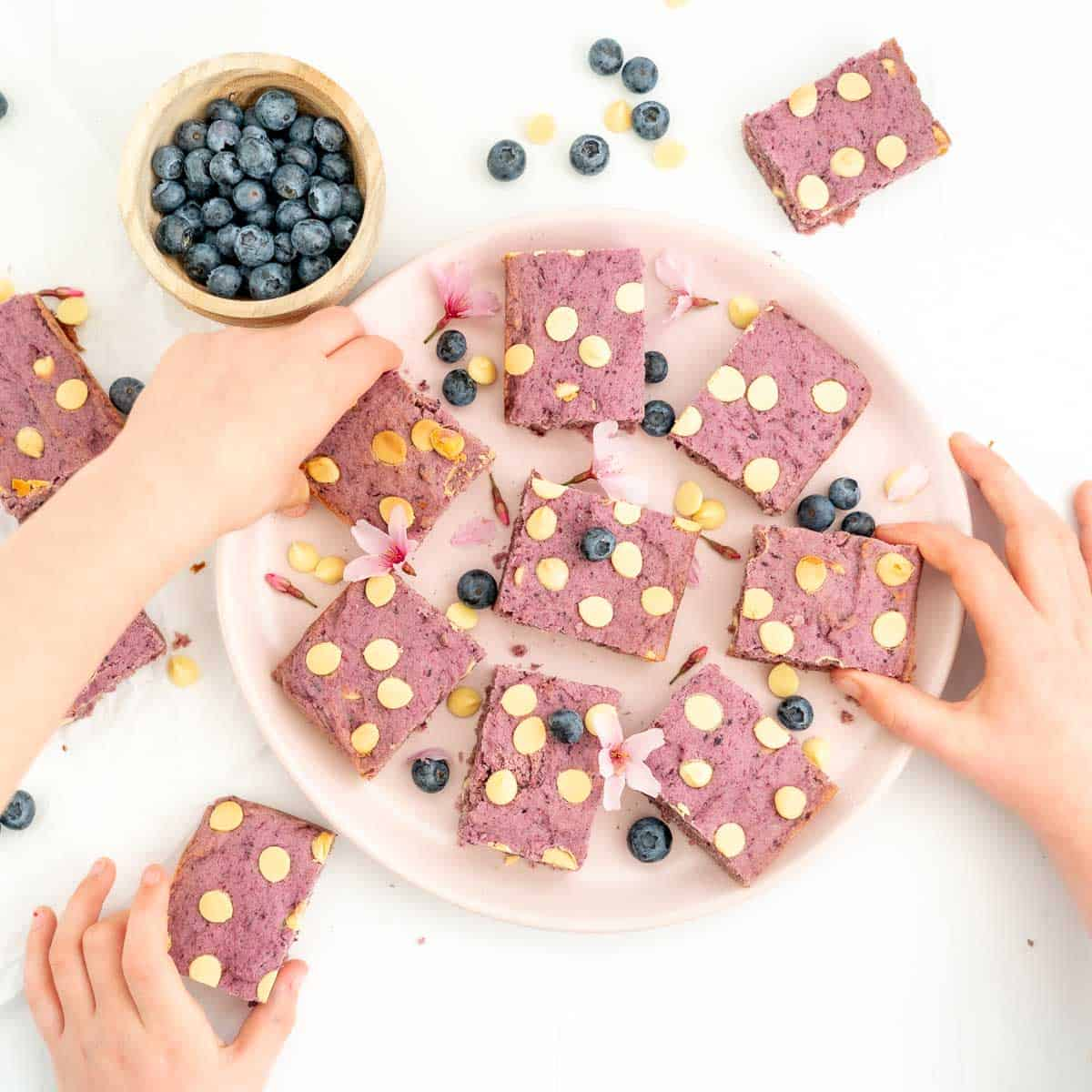 Three children's hands reaching for purple cookie bars sitting on a pink plate.