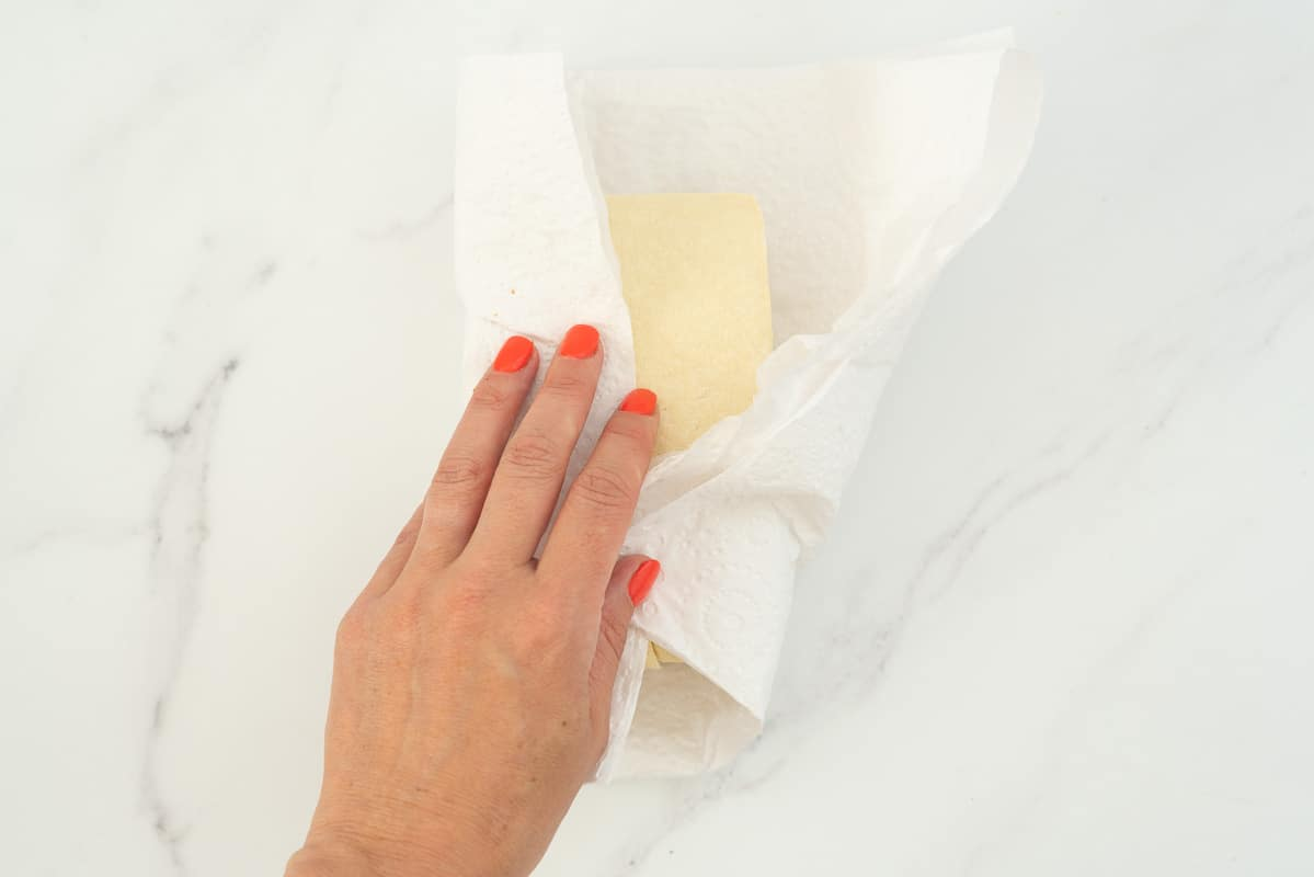 A block of firm tofu wrapped in paper towel.